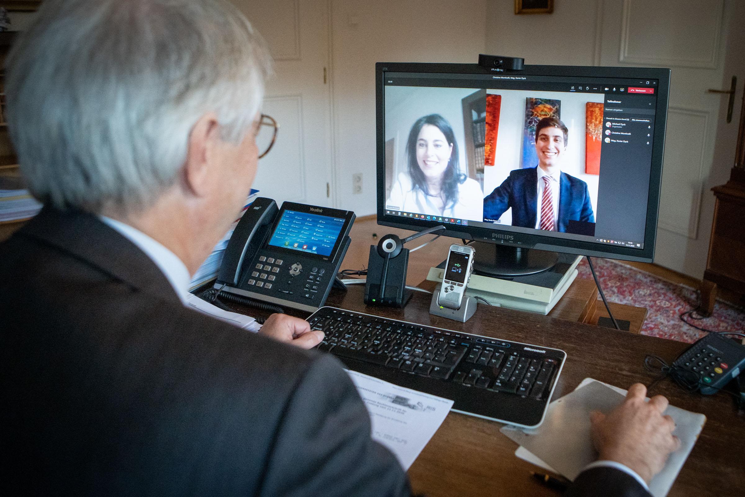 Dr. Michael Dyck sitzt am Computer bei einer Videokonferenz: Am PC-Bildschirm sieht man Dr. Christine Monticelli und Mag. Xavier Dyck.