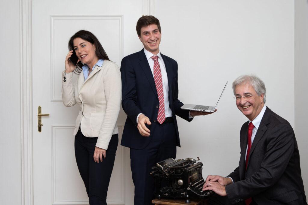 Ganzkörperbild der drei Rechtsanwälte von Dyck & Monticelli: Dr. Christine Monticelli telefoniert, Mag. Xavier Dyck hält einen Laptop in der Hand, Dr. Michael Dyck sitzt an einer alten Schreibmaschine.